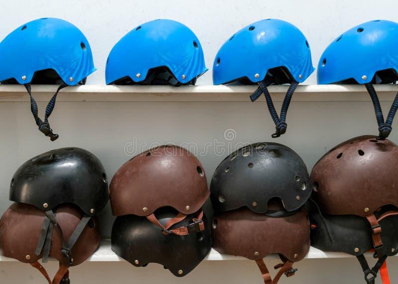 Cascos extremos azules, negros y marrones del deporte en el estante con el wh foto de archivo