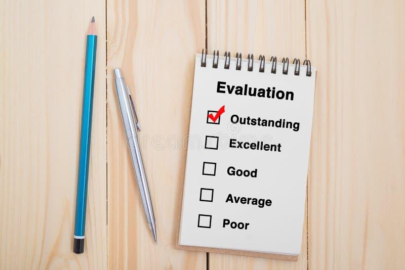 Case à cocher d'évaluation des performances sur le carnet avec le stylo et le crayon photo stock