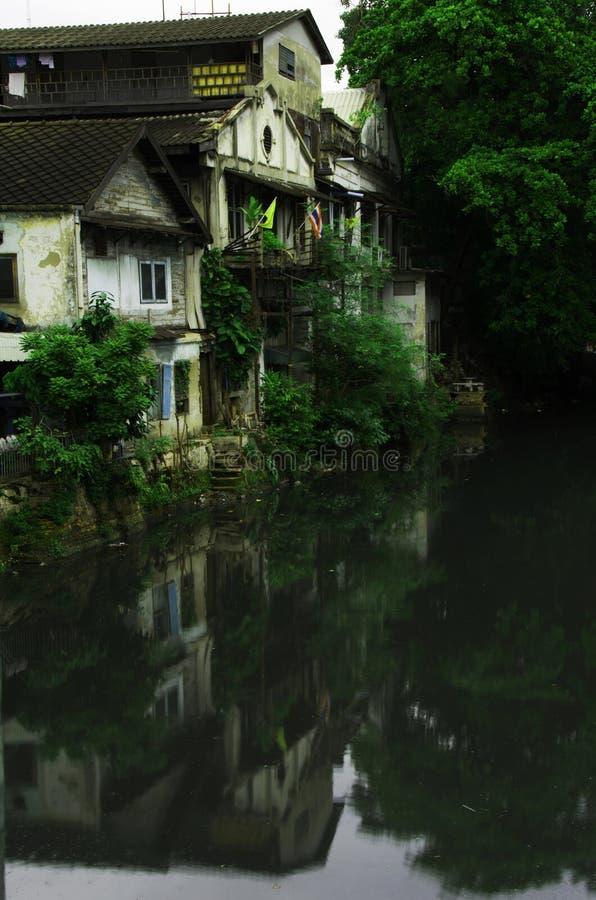 Case bianche di riflessione vecchie nel fiume in Tailandia immagini stock libere da diritti