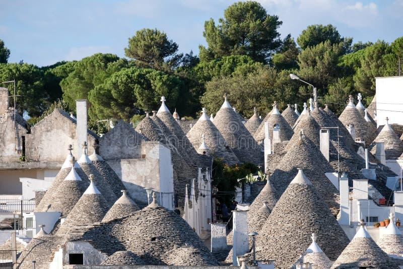 Case conico-coperte imbiancate tradizionali nell'area di Rione Monti della città di Alberobello in Puglia, Italia del sud fotografia stock