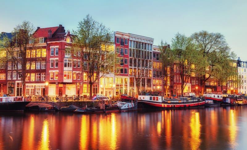 Case del canale di Amsterdam al crepuscolo con le riflessioni vibranti, Neth fotografia stock libera da diritti