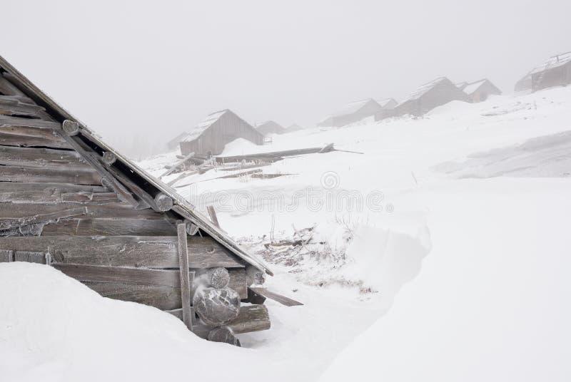 Case di abbandono sotto neve e foschia fotografie stock libere da diritti