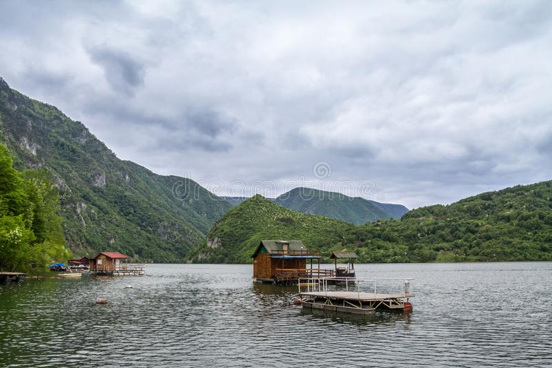 Case di galleggiamento di Fishemen sul lago Perucac, sul fiume di Drina, in Serbia occidentale, circondata da una valle e da un c fotografie stock libere da diritti