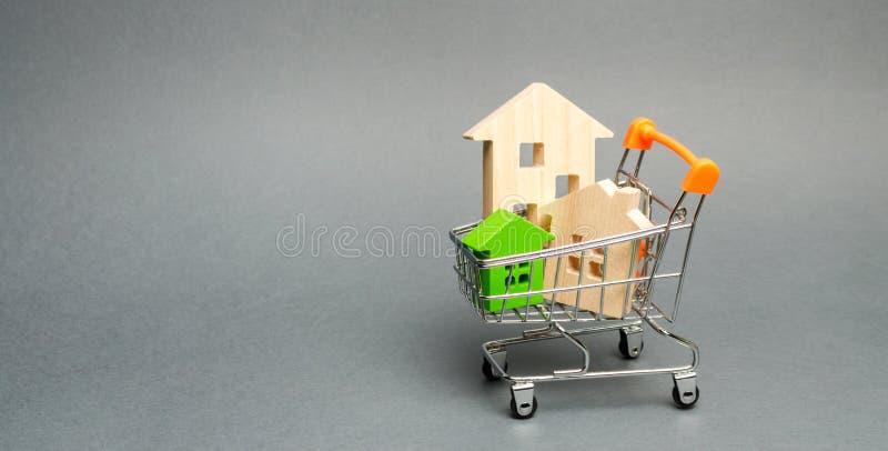 Case di legno in un carrello del supermercato Il concetto di acquisto una casa o dell'appartamento Alloggiamento acquistabile Pre immagine stock