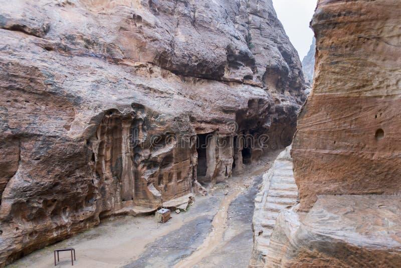 Case di pietra in rocce curve a poco parco archeologico di PETRA al giorno piovoso di inverno freddo immagine stock libera da diritti