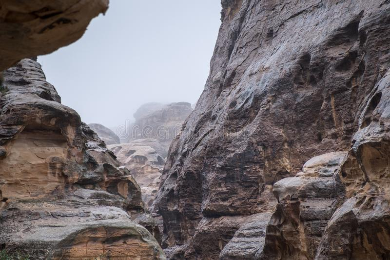 Case di pietra in rocce curve a poco parco archeologico di PETRA al giorno piovoso di inverno freddo fotografie stock libere da diritti