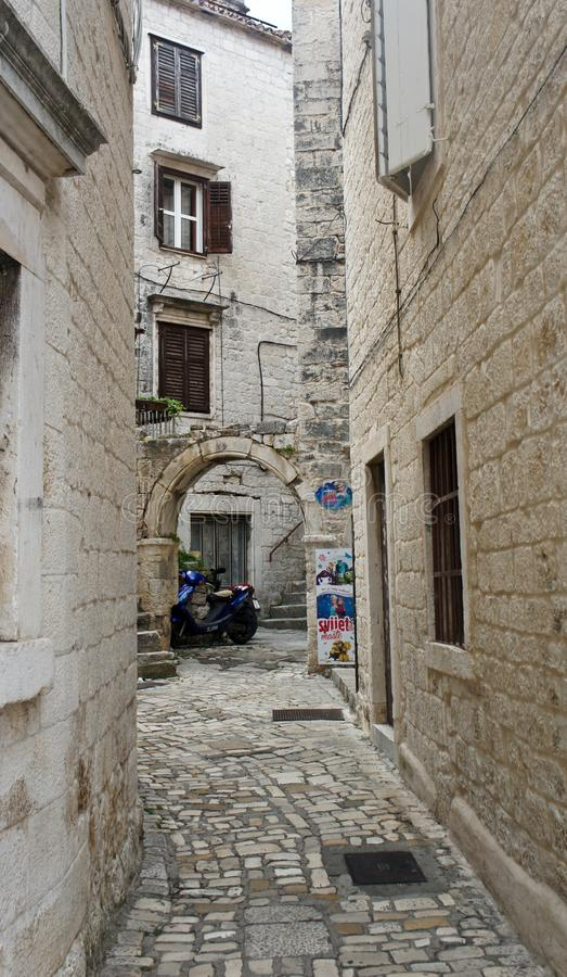 Case di pietra in via stretta di vecchia città, bella architettura con l'arco, giorno soleggiato, Traù, Dalmazia, Croazia fotografie stock