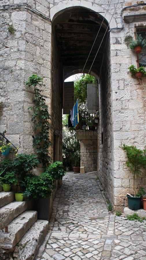 Case di pietra in via stretta di vecchia città, bella architettura con l'arco, piante e scale, Traù, Dalmazia, Croazia fotografie stock libere da diritti