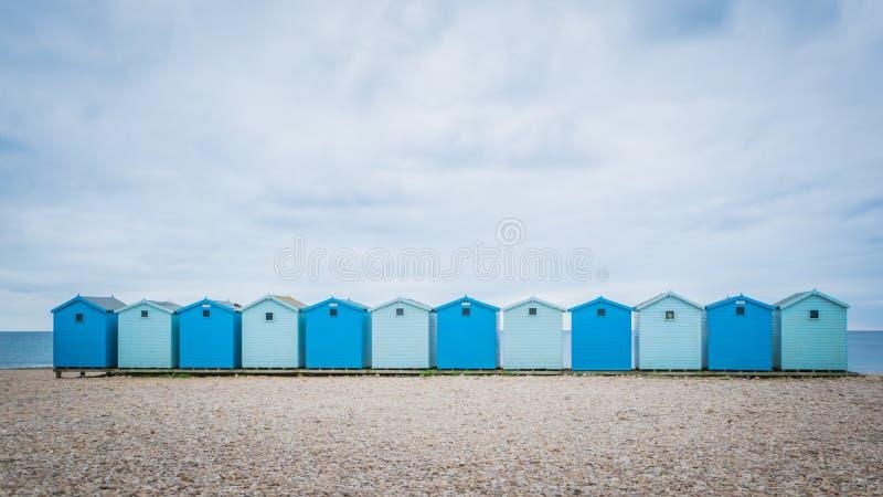 Case di spiaggia blu britanniche vicino a Charmouth in Dorset, Regno Unito fotografia stock