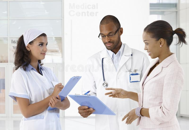 Case discussion at medical center. Doctor nurse and patient discussing case at medical center royalty free stock images