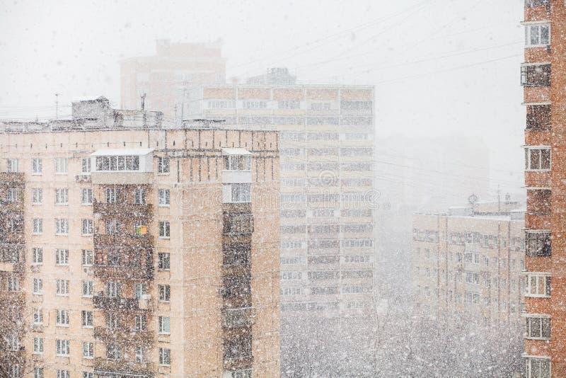 Case e precipitazioni nevose urbane in città nell'inverno immagini stock