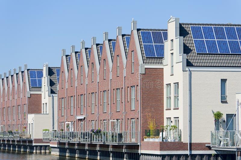 Case olandesi moderne con i comitati solari sul tetto fotografia stock