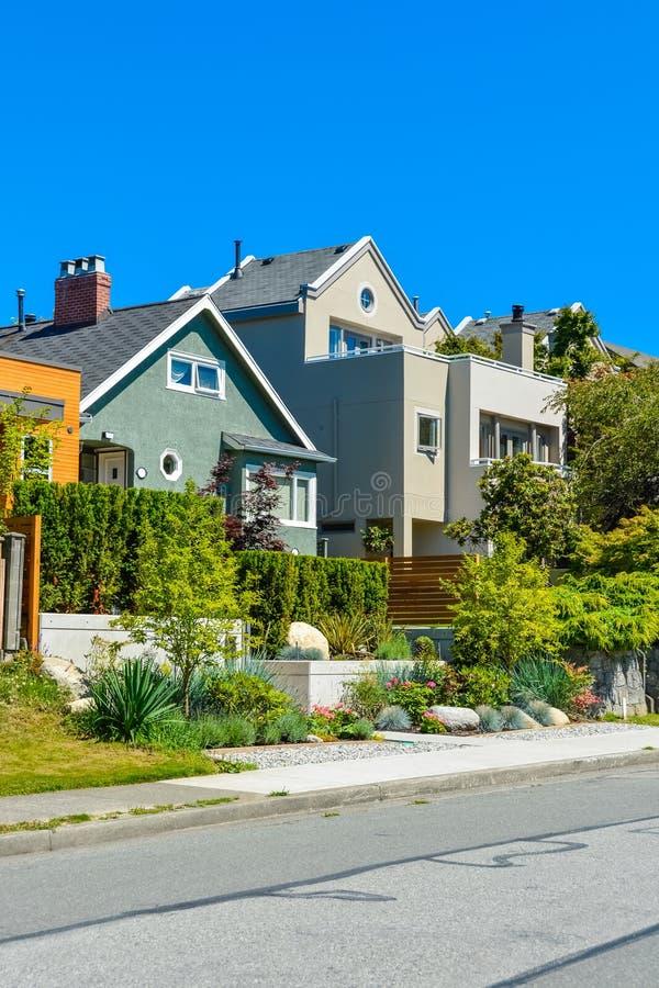 Case residenziali moderne sulla via con le iarde anteriori abbellite sui terrazzi fotografia stock libera da diritti