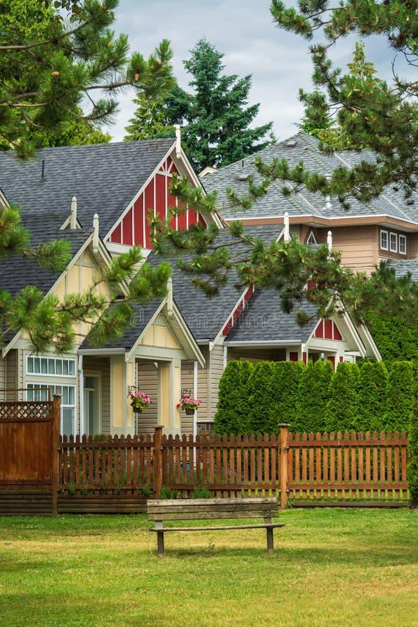 Case residenziali variopinte con il banco woodent sul prato inglese del parco vicino fotografia stock libera da diritti