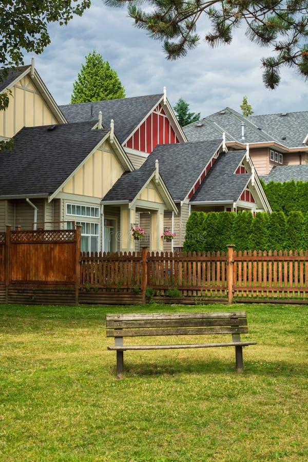 Case residenziali variopinte con il banco woodent sul prato inglese del parco vicino immagine stock libera da diritti