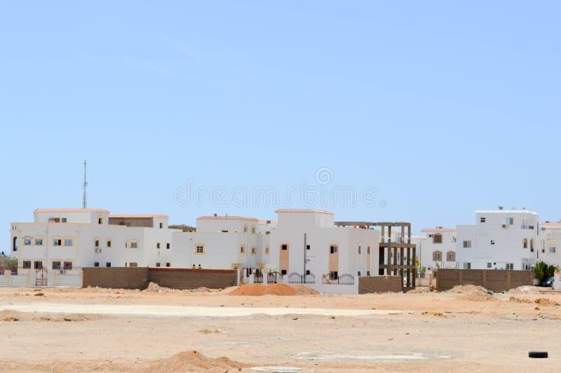 Case rettangolari arabe nel deserto con le finestre contro lo sfondo di giallo sabbia e del cielo blu immagini stock