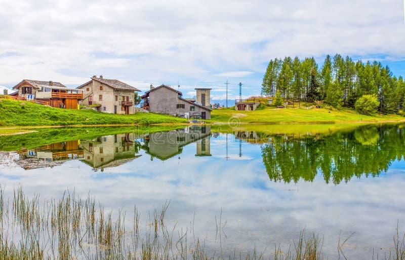 Case riflesse nel lago Lod vicino al villaggio del camoscio nel ` Aosta, Italia di Val D fotografia stock libera da diritti