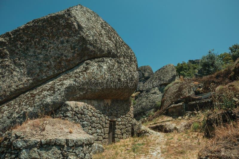 Case rustiche con la parete di pietra dentro grande roccia a Monsanto immagini stock libere da diritti