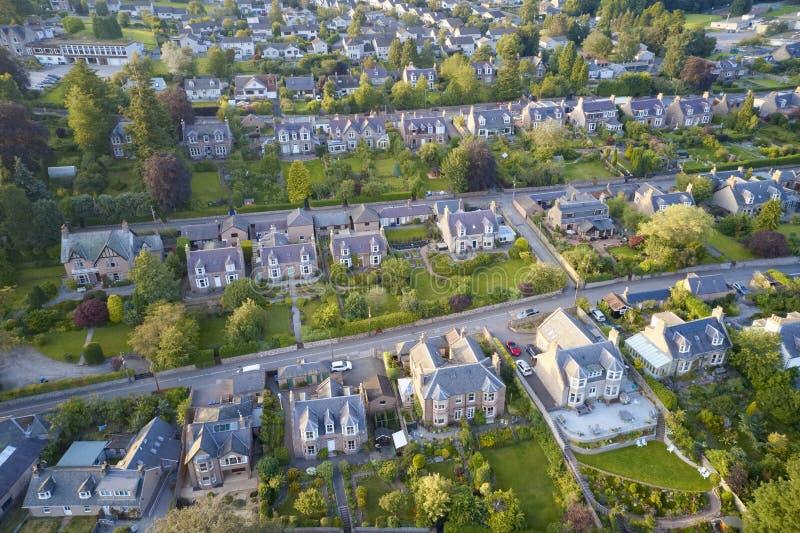 Case suburbane nella vista aerea di fila di estate che illumina i giardini immagine stock