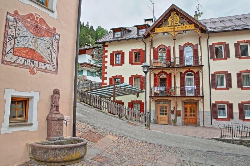 Case tradizionali su un quadrato vicino alla chiesa cattolica in Santa Cristina con una fontana e una meridiana nella priorità al fotografie stock