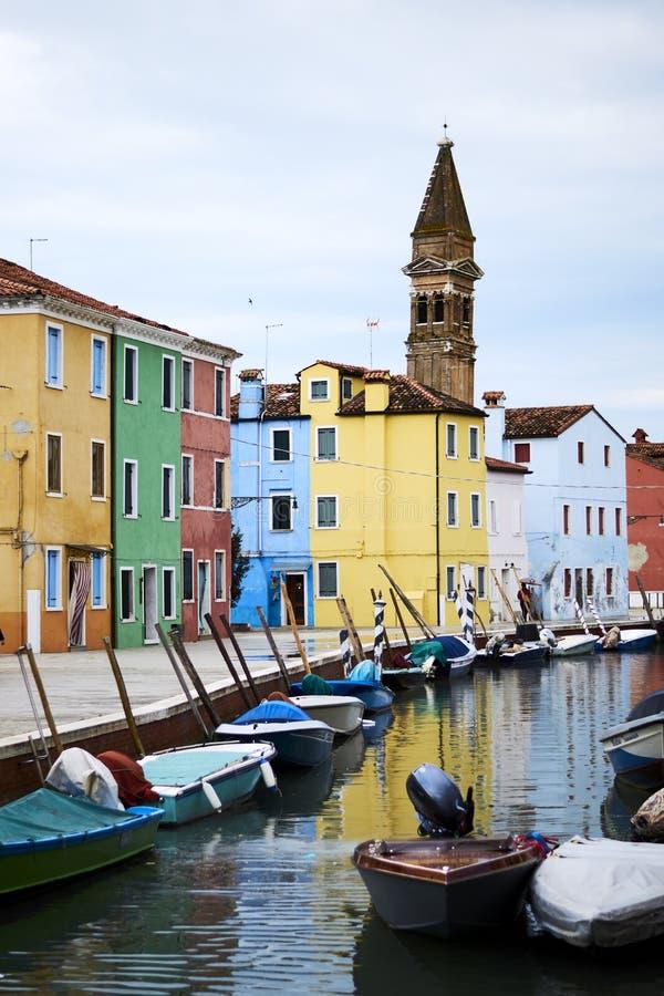 Case variopinte in Bruno, Venezia con una chiesa dietro fotografia stock libera da diritti