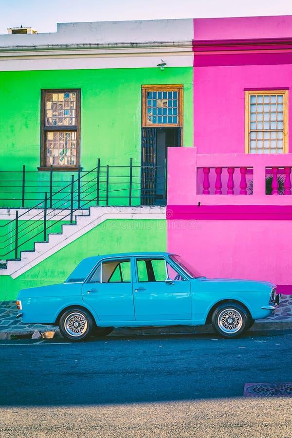 Case variopinte della BO Kaap e retro automobile blu a Cape Town immagine stock