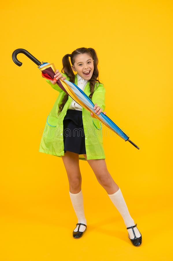 In case it will rain. Happy small schoolchild in raincoat holding umbrella against rain. Cute little girl with fashion stock photos