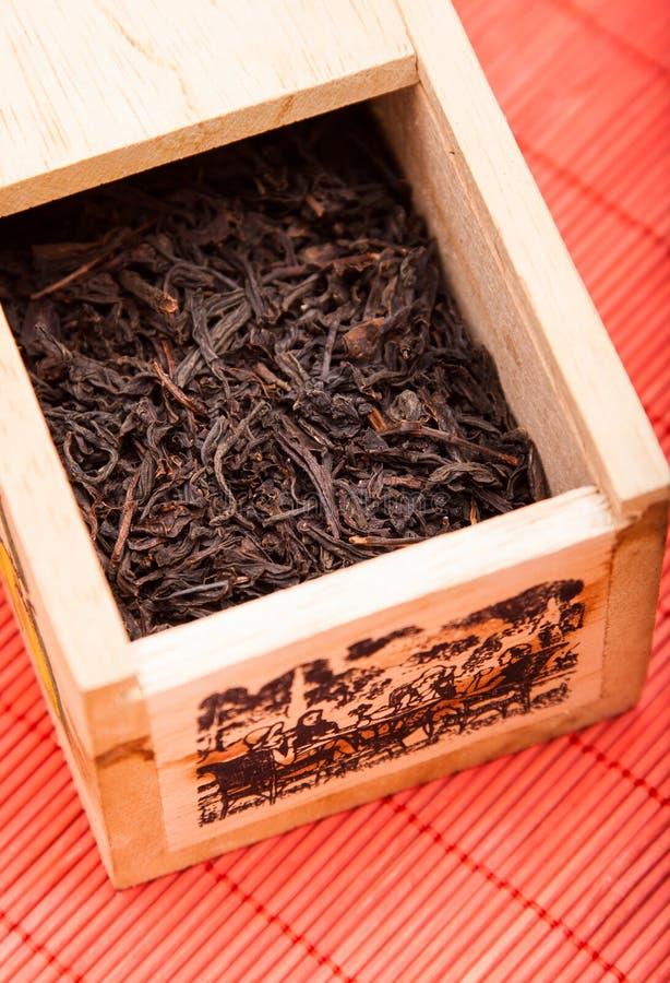Casella con tè nero sulla stuoia rossa immagine stock