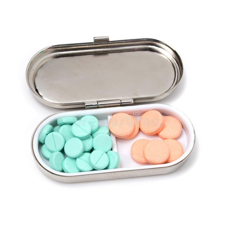 Casella della pillola dell'oggetto d'antiquariato con i ridurre in pani verdi ed arancioni fotografia stock libera da diritti