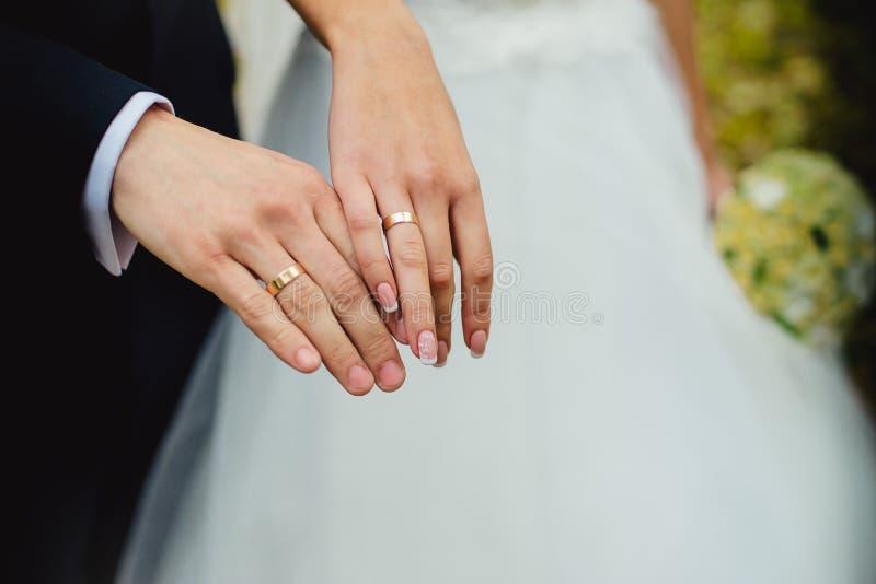 Casese nuevamente las manos del par con los anillos de bodas imagenes de archivo