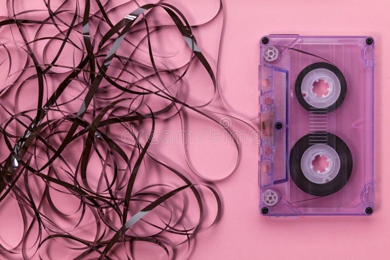 Casete audio compacto en fondo rosado con la cinta enredada imagenes de archivo