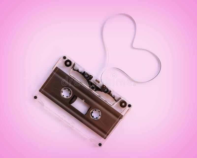 Casete audio transl?cido con la cinta magn?tica en la forma de un coraz?n aislado en fondo rosado fotos de archivo
