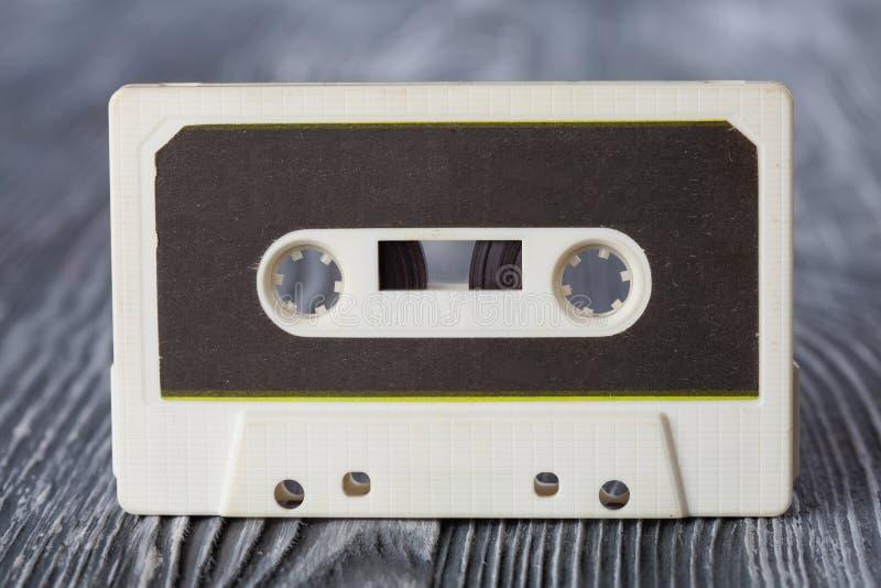 Casete compacto del vintage con el formato de grabación magnético para el audio y el aparato de lectura Fondo de madera gris Foco imagen de archivo libre de regalías