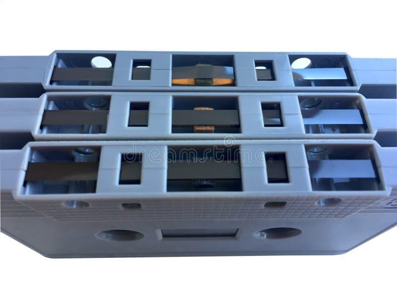 Casete de cinta gris clásico viejo en la capa de la película aislada en el fondo blanco fotos de archivo