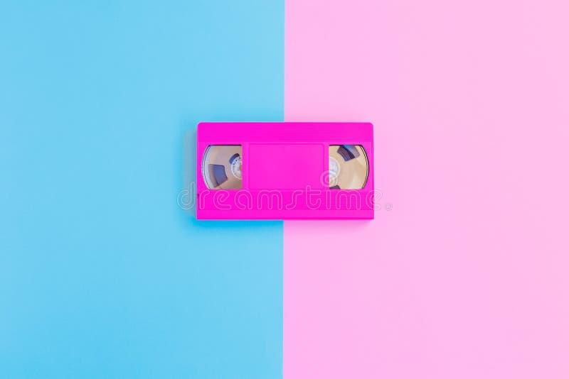 Casete de VHS en rosa suave y fondo de papel azul Concepto mínimo Concepto creativo Concepto del cine fotos de archivo