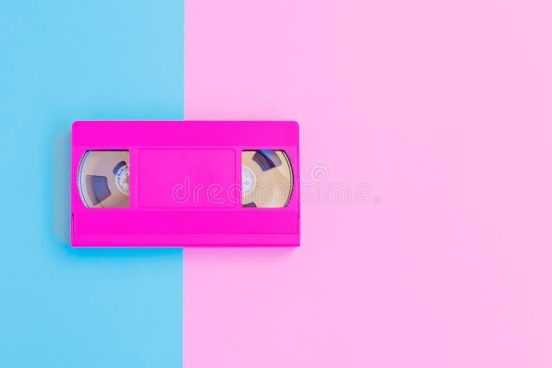 Casete de VHS en rosa suave y fondo de papel azul Concepto mínimo Concepto creativo Concepto del cine Arte pop foto de archivo libre de regalías