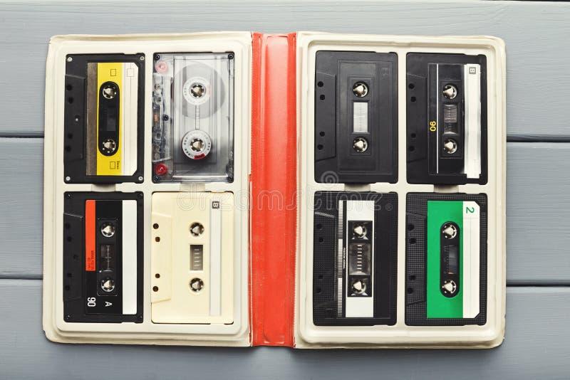 Casetes audios del vintage en el organizador blanco en la tabla gris, visión superior fotografía de archivo