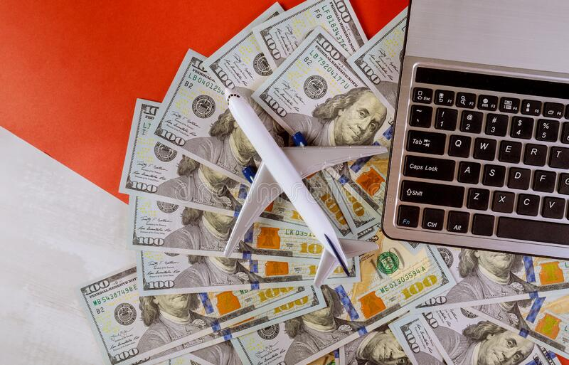 Cash in american dollar banknotes with plastic airplane model and computer keyboard. Cash in american dollar banknotes with plastic airplane model and laptop royalty free stock image