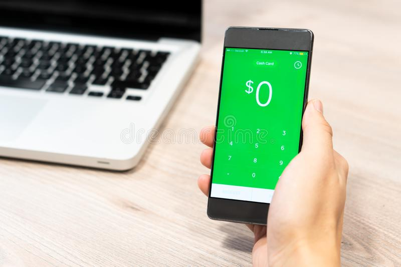 Cash App by Square inc displayed on smartphone held by human hand next to computer laptop - Slovenia 13.02.2019 stock photography