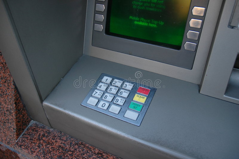 Cash or ATM machine. In a red marble building. Can only see the entry key pad and some of the green screen royalty free stock photo