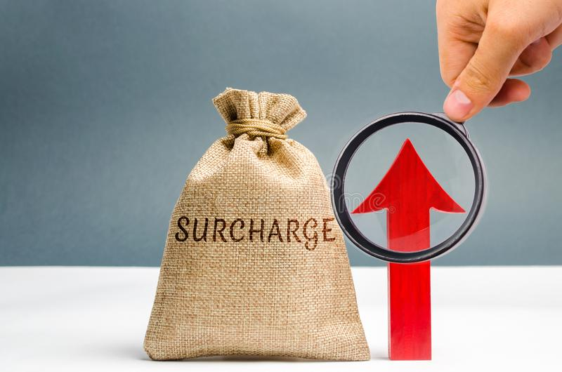 A cash bag with the word Surcharge and a red up arrow. Increase in fine and penalties for violating. The system of cumulative. Penalties. Progressive system stock photos