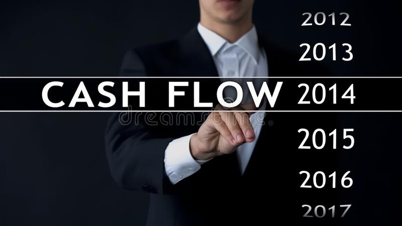 Cash flow for 2014, businessman selects financial report on virtual screen stock photo