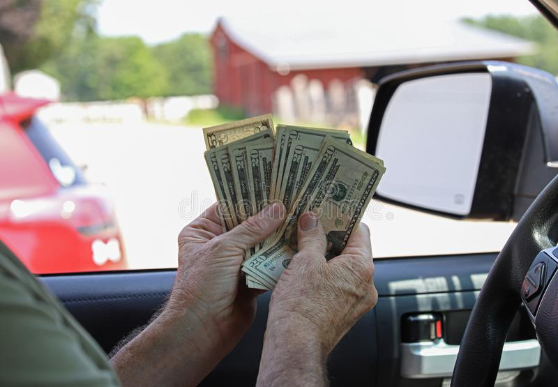 Cash In Hand. Holding cash in hand twenty dollar bills fanned out while sitting in a truck royalty free stock photo