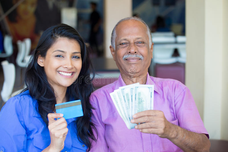 Cash, money, credit, exchange. Closeup portrait rich elderly gentleman in pink shirt and lady in blue top holding greenbacks and credit card. Booming economy royalty free stock images