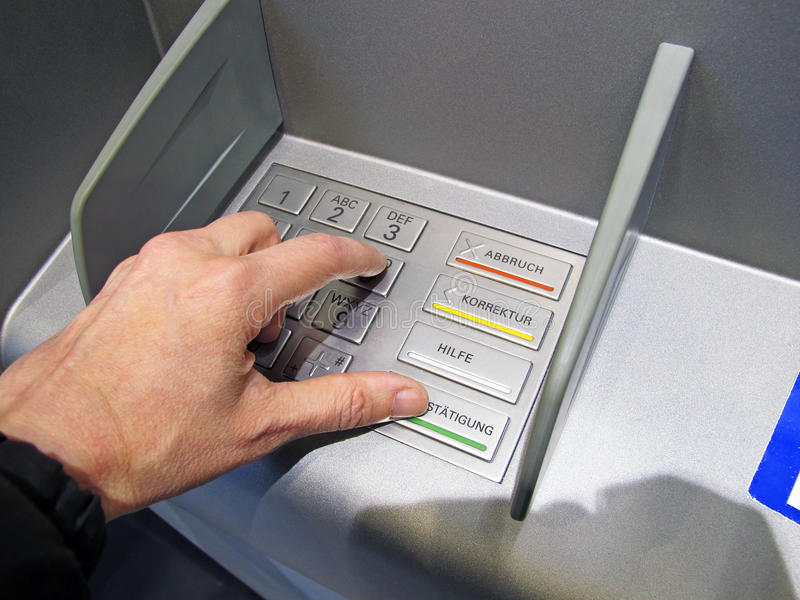 Cash point. Cahspoint bancomat with hand dialing the pin code stock photos
