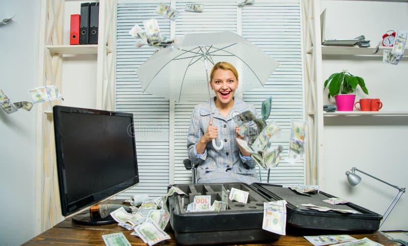 Cash rain concept. Money falling as rain. Woman business lady or accountant under umbrella. Financial success. Accountant with pile money hide under umbrella royalty free stock photos