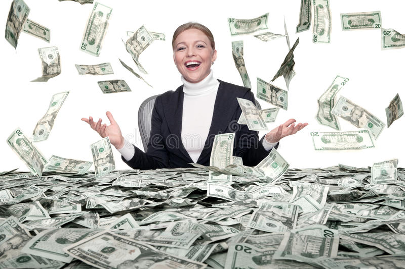 Cash rain. Portrait of young woman sitting behind the table full of cash stock image