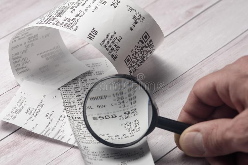 Cash receipts on the table are considered through a magnifying glass royalty free stock photos