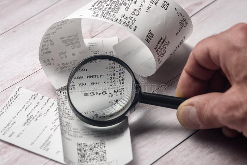 Cash receipts on the table are considered through a magnifying glass stock photo