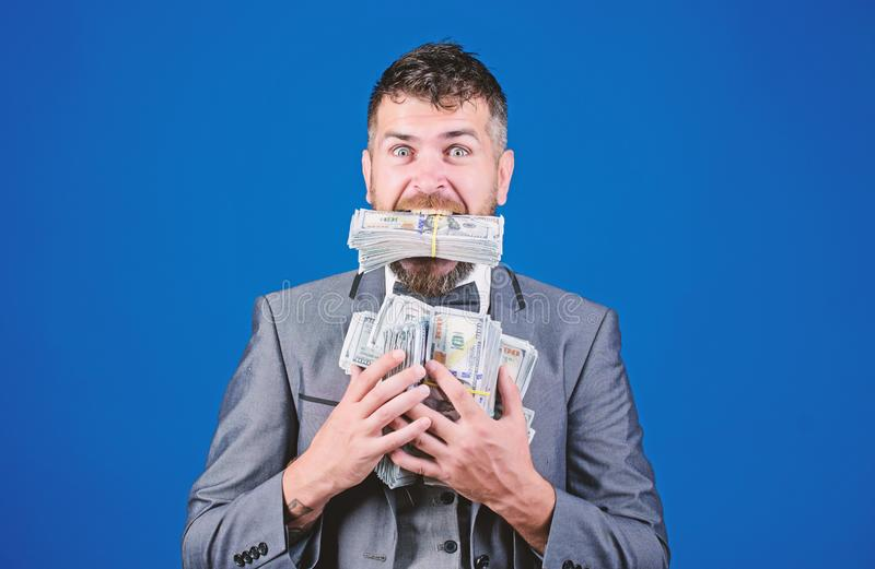 Cash transaction business. Easy cash loan. Man formal suit hold many dollar banknotes blue background. Businessman got stock photography